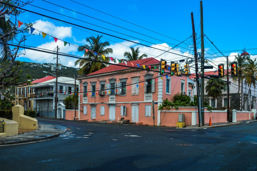 Old colonial architecture and streets like this are prevalent all across the old part of Charlotte Amalie. Photo features colorful buildings, vehicles, and store fronts.